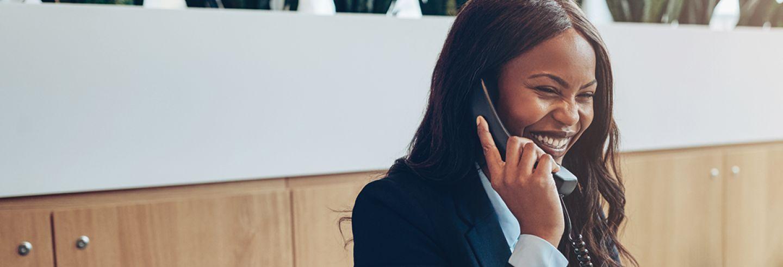 Vrouw zit lachend aan bureau met telefoon aan haar oor